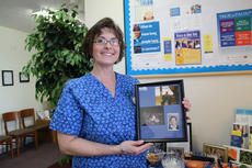 """<div class=""""source"""">Stephanie Hornback/The Kentucky Standard</div><div class=""""image-desc"""">Lisa Sosnin holds family photos that are displayed in the Bardstown doctor's office she and her husband run. </div><div class=""""buy-pic""""><a href=""""/photo_select/24657"""">Buy this photo</a></div>"""