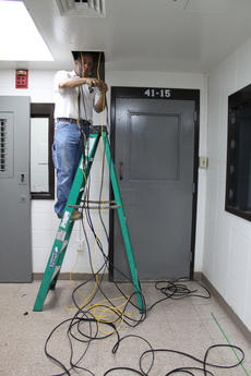 "<div class=""source"">ERIN L. MCCOY/The Kentucky Standard</div><div class=""image-desc"">Chris Norris, a head technician at Advanced Surveillance Inc., helps install a 40-camera surveillance system at the Nelson County Jail Friday. Two panic buttons in the jail will transmit live video from the jail to the Nelson County Dispatch Center when pressed. </div><div class=""buy-pic""><a href=""/photo_select/30011"">Buy this photo</a></div>"