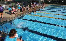 """<div class=""""source"""">PETER W. ZUBATY/The Kentucky Standard</div><div class=""""image-desc"""">Parents and fans are able to follow along with meet officials at a recent Bardstown Barracudas youth swim meet via a phone app called Meet Central. Barracudas coach Robin Leake (standing, with clipboard) says the program helps speed meets along and enables parents and swimmers to see real-time results.</div><div class=""""buy-pic""""></div>"""