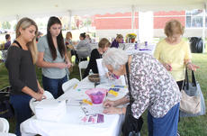 """<div class=""""source"""">RANDY PATRICK/The Kentucky Standard</div><div class=""""image-desc"""">Hazel O' Bryan of New Haven signs a form at the Kentucky CancerLinks table at the health fair where UK students Ashley Bergmann and Kayla Dreves were volunteering.</div><div class=""""buy-pic""""><a href=""""/photo_select/89930"""">Buy this photo</a></div>"""