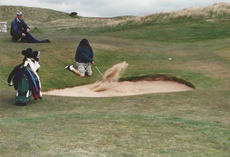 """<div class=""""source"""">PHOTO SUBMITTED</div><div class=""""image-desc"""">You never know what kind of shot you might encounter when you play links golf in England or Scotland. Here, column writer Dennis George gets creative on a bunker shot at Muirfield.</div><div class=""""buy-pic""""></div>"""
