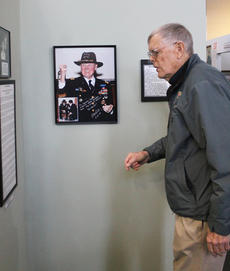 """<div class=""""source"""">RANDY PATRICK/The Kentucky Standard</div><div class=""""image-desc"""">Bob Llewellyn, curator of the museums, looks at part of the Hal Moore collection at the war museum named  for him. The photograph on wall shows Moore, of Bardstown, long after his service in Vietnam.</div><div class=""""buy-pic""""><a href=""""/photo_select/93487"""">Buy this photo</a></div>"""