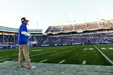 "<div class=""source"">Chet White/UK Athletics</div><div class=""image-desc"">Kentucky offensive coordinator and Bardstown native Neal Brown surveys the field during the annual Blue-White spring game in April. More than 50,000 fans attended the game, which is more than double the previous spring game record attendance. </div><div class=""buy-pic""></div>"