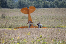 "<div class=""source"">RANDY PATRICK/The Kentucky Standard</div><div class=""image-desc"">Two men look at the wreckage of a Carbon Cub that went down in a soy bean field on a farm near the end of the Samuels Field runway Thursday night. The FAA was investigating the crash Friday.</div><div class=""buy-pic""><a href=""/photo_select/89862"">Buy this photo</a></div>"