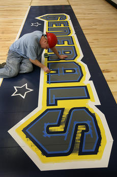 """<div class=""""source"""">Tom Dekle/Nelson County Schools</div><div class=""""image-desc"""">Michael Chesser, a subcontractor with Martin Flooring out of Louisville works on the end zone graphics at the gymnasium. </div><div class=""""buy-pic""""></div>"""