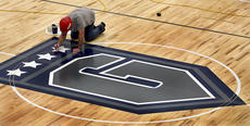 """<div class=""""source"""">Tom Dekle/Nelson County Schools</div><div class=""""image-desc"""">Russ Simon, a subcontractor with Martin Flooring out of Louisville does detail work on the Generals logo at halfcourt of the Thomas Nelson gym.</div><div class=""""buy-pic""""></div>"""