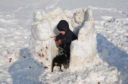 Rylan vonRoenn, 5, enjoys his snow fort with his dog, Rottie, that he made with his papaw, Jeff McMichael