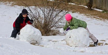Siblings Mikey (left) and Sarah Rouse, of Bardstown, work on building a pair of snowmen recently after three inches of perfect packing snow fell across the area.