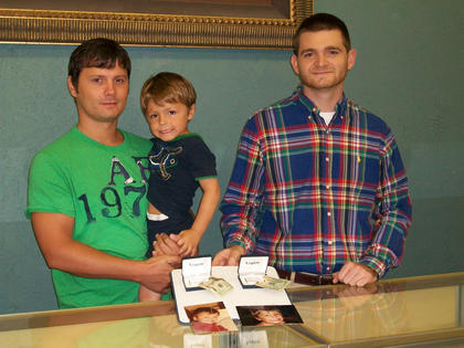 Wesley Parrent, left, holds his son, Landen, as they receive two matching engraved money clips containing $20 from Marshall's Jewelers' employee Eric Rosenblatt. Wesley and Landen won The Kentucky Standard's father/son look alike contest.
