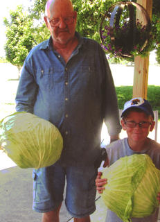 Charles A. Downs and grandson, Layne Berry, hold two heads of cabbage — one 10 pounds and the other 8 pounds — grown in Downs' back yard. The circumference of the 10-pound head was 45 inches.