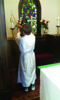 """Over summer break, Trever Cissell and his younger brother, Tanner Cissell, practiced and received the title of  """"acolyte"""" at their church. In this photo, Trever is extinguishing the candles after the procession."""