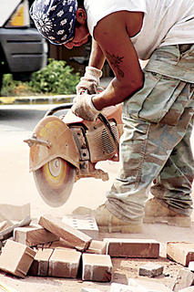 AUGUST 2010: A Streetscape worker cuts brick for a new sidewalk at the corner of Flaget Avenue and North Third Street near Town & Country Bank. (Published Aug. 27, 2010.)