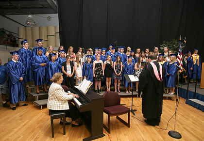 Choral and Band Director Marc Monroe leads a chorus of graduate.