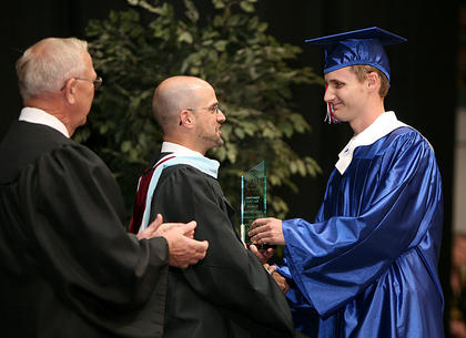 Nelson County Schools Superintendent Anthony Orr shakes the hand of a 2011 Nelson County High School graduate June 3. Board member Frank Hall is at left.