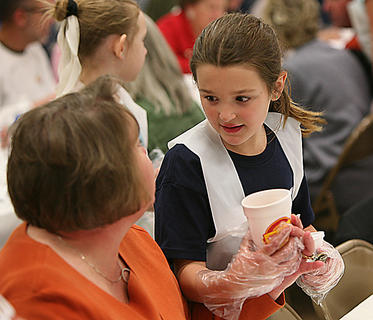 Natalie Skinner, right, takes a request from Kay Greenwell during the 95th annual Boston Oyster Supper, Saturday in Boston. Natalie, a third grader, was one of several dozen Boston School students that helped during the event. The children earned community service credit and tips.
