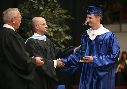 Joseph Taylor receives a special award from superintendent Anthony Orr for 12 years of perfect attendance. Also pictured is the longest serving school board member, Frank Hall. Taylor was honored at the outset of graduation ceremonies and was the first senior to cross the stage.