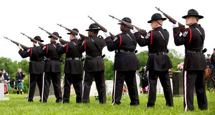 An honor guard fires a 21-gun salute for fallen Bardstown Police Officer Jason Ellis Thursday.