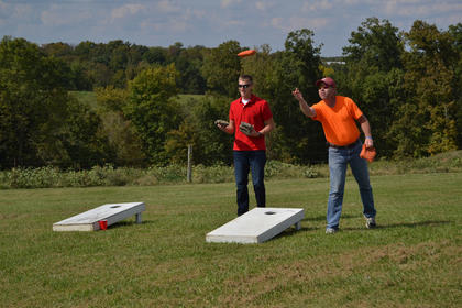 Tyler Milburn and Timothy Prather play cornhole at Young Farmers Day Saturday.