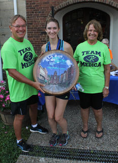 Margaret and Leon Claywell of Medica Pharmacy and Wellness Center present the first-place prize to the overall winner of the women's competition in the Run for the Health of It 5K, Monica Musk, who won despite the fact that she started late.