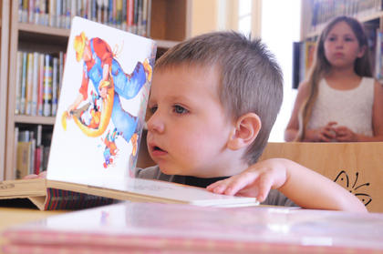 Hunter Pike, 2, Bloomfield, looks at a picture book in the children's section of the Bloomfield library at the June 10 opening.
