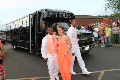 Dee Yocum, left, and Kindsay Riney wear color-coordinated orange and white prom attire as they exit a bus they and other couples used to take them to the Bardstown High School prom. Walking behind them are Alexis Brewer and Devonte Grundy.