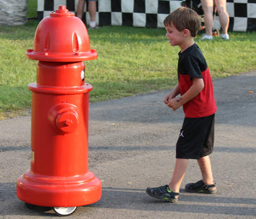 Blake Mudd, 4, has a conversation with a fire hydrant. The robotic hydrant was remotely controlled by Bardstown-Nelson County firefighters from inside a trailer.
