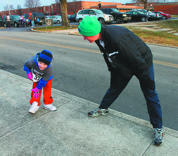 Bob Kelly and his grandson, Connor Henson, 7, stretch before the Tiger Run 5K race Saturday.