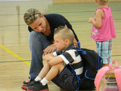 ABOVE — A concerned mother kneels next to her distraught son in the Boston School gymnasium. Many children suffer from separation anxiety on their first day of kindergarten.