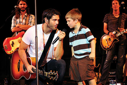 Aiden Henley, 7, helps Chuck Wicks sing the last song of the show Aug. 14 at the J. Dan Talbott Amphitheater.