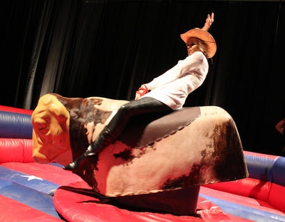 Lyquita Culver, Bardstown, hangs on as the mechanical bull bucks at Boots & Bourbon Thursday night.