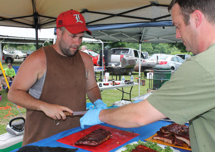 Brian Green, left, and Jason McCorkle, slice meat for their ribs entry.
