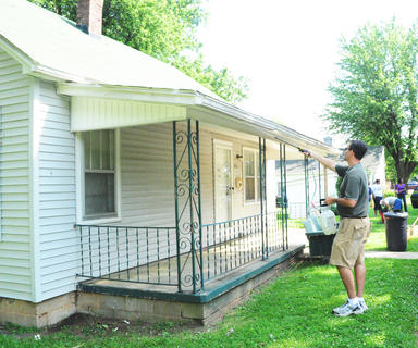 Peter Trzop, commander of American Legion Old Kentucky Home Post 121, sprays a pest control agent on the roof to deal with a bug problem.