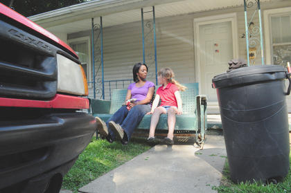 Lucretia Young and Peter Trzop's daughter, Reagan, 6, take a break on Ada Hickman's porch swing.
