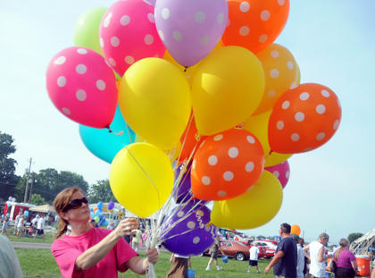 Sarah Lawson, Bardstown, gives balloons away at the Salt River Electric annual picnic Monday.