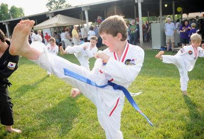 Tristan Boggs practices a kick with students from Y-Lee's School of Martial Arts and Associated Schools Monday at The Salt River Electric Picnic.