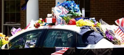 Flowers, a baseball cap, candles and handwritten notes were some of the tributes left for Bardstown Police Officer Jason Ellis on a cruiser outside the Bardstown Police station over Memorial Day weekend.