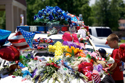 Bryce Riley, the son of Nelson County Deputy Reece Riley, who was close friends with the Ellis family, looks over the tributes left on a police cruiser Monday in memory of slain Bardstown Police Officer Jason Ellis.
