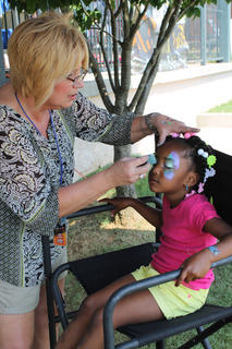 Kenya Tinsley, 5, of Louisville, sits patiently while she gets her face painted at a Day Out with Thomas at the Kentucky Railway Museum.