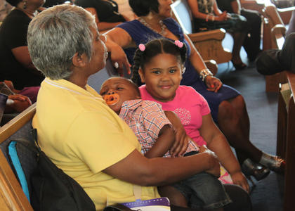 Leora English, Louisville, holds her daughter's nephew, 16-month-old Shawn Stinson Jr., as she listens to Sen. Georgia Powers speak at Second Baptist Church in Fairfield June 3. Also listening to Powers speak is English's granddaughter, 4-year-old Breonna Green. Stinson is the son of the church's associate pastor, the Rev. Shawn Stinson.