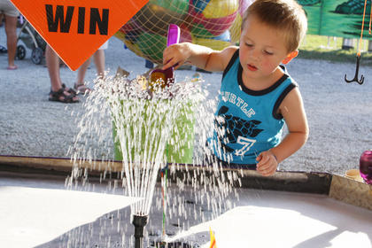 Reese Centers, of Bardstown, concentrates as he plays at the fishpond at the Nelson County Fair.