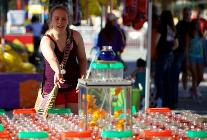 Lindsey Astrom, from Bardstown, rises to toss a ping pong ball into a bowl to win a goldfish at the Nelson County Fair Monday.