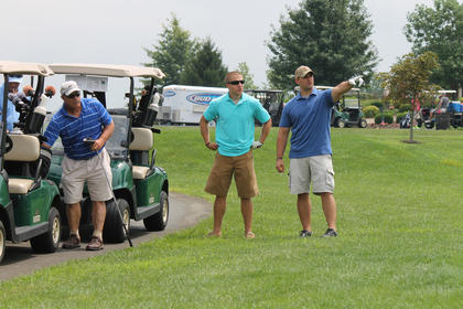 Aaron Clark points out something on the golf course to Kyler Wright as Aaron's father, Lewis Clark, prepares to hit a drive Saturday in the FOP's Jason Ellis Memorial Golf Scramble. Behind Lewis Clark is his other son, Michael Clark. He and Wright are law enforcement officers.