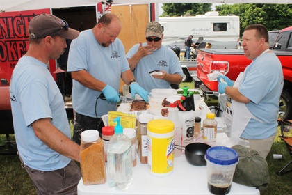 Members of the winning backyard barbecue team, Midnight Smokers of Mount Juliet, Tenn., slice up ribs to present to the judges.