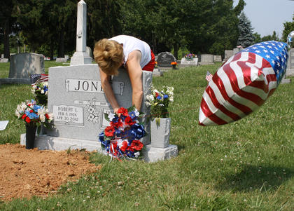 Diana Jones, Bardstown, tries to find the perfect spot for a wreath on her father, Robert's, grave on Memorial Day May 28. Diana, along with her mother, Dorothy, visited Robert's grave to place an American Flag balloon, wreath and flowers. Robert, who passed away in late April, was a veteran of the United States Navy.