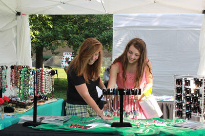 Kaleigh Ballinger, right, and Nicole Ballinger, LaGrange, look at a selection of jewelry made by Valerie Crabtree, Bardstown, at the