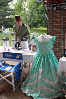 "John Rowan (Charlie Beam) checks out the silent auction items, including a dress worn in a 1986 production of ""The Stephen Foster Story,"" at the Opening Night Gala & Garden Party June 11."