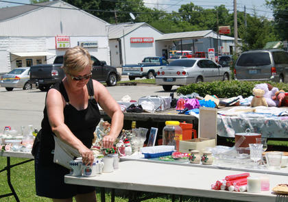 Carolyn Sweasy, Cox's Creek, arranges items for sale in her mother's yard in Fairfield during the first day of the 2011 Fairfield Days and Homecoming June 25. Sweasy's mother, Martha Richardson, said she has collected items throughout the year to sell at the event every year since it started in 1995. Granddaughter Melinda Royalty, Taylorsville, also turned out to help.