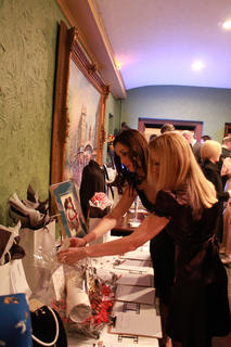 Eulanda Clark, Bardstown, left, and Rhonée Rodgers, Villa Hills, Kentucky, look at a silent auction item at the 2011 Beautiful Dreamer Ball.