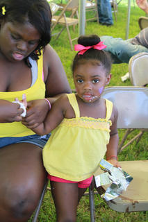 Jazlyn Kimberland, Bardstown, looks after her young friend, Amareeyah Sawyer, 3, after getting her face painted and peeling open an ice cream bar at the 2011 Fairfield Days and Homecoming June 25.