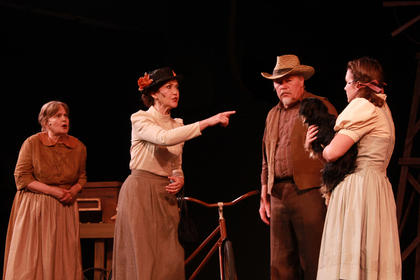 Aunt Em (Lee Evans) and Uncle Henry (Charlie Beam) look on as Miss Gultch (Jan McIntire) accuses Dorothy's dog of biting her. Trish Epperson portrays Dorothy, while a yortese named Molly portrays Toto.